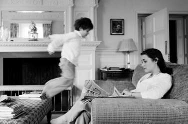 A small child leaps onto a sofa while his mother attempts to read.