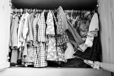 A small child plays hide and seek in a wardrobe during a family photo shoot.