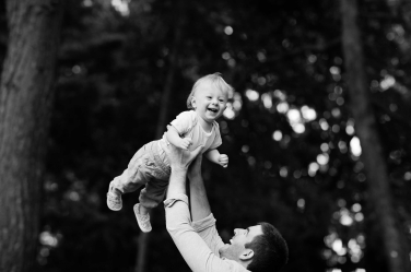 A small boy is lifted high into the air by his father.