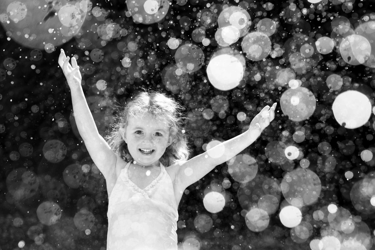 A little girl dances in the water thrown out by a garden sprinkler during this family portrait shoot.