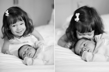 A big toddler sister snuggles into her brand new sibling.