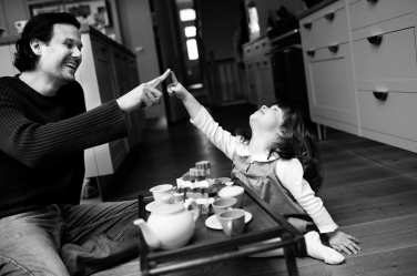 This little girl has a toddler's tea party with her father. The special moments are part of a baby's first year of photos by London professional photographer Helen Bartlett.