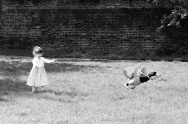 A girl watches a duck fly away in delight during a family professional photo session in London.