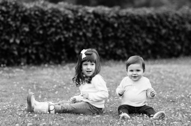 A brother and sister sit on the grass for black and white portraits by London professional photographer Helen Bartlett.