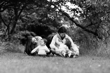 Parents and their two children sit on a manicured lawn for a family portrait in black and white.