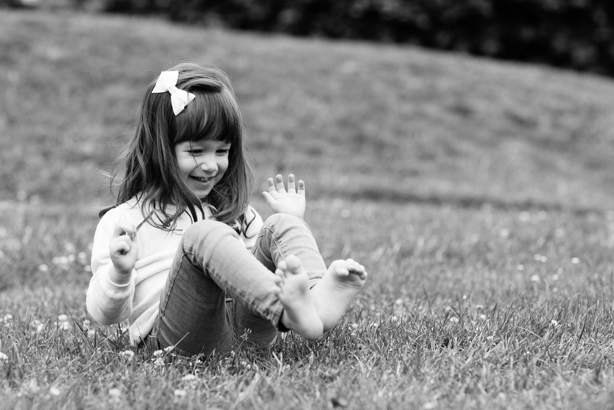 Summer grass tickles the feet of this little girl during her photo shoot with photographer Helen Bartlett.