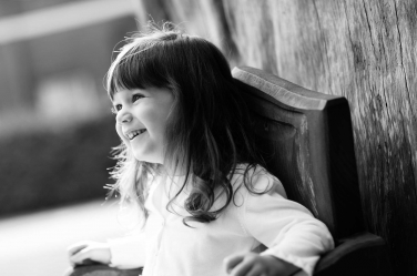 This toddler girl is lit with natural light in a black and white portrait by London photographer Helen Bartlett.