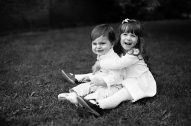 A sister cuddles her brother for a portrait on the grass as part of baby's first year of portraits by London photographer Helen Bartlett.