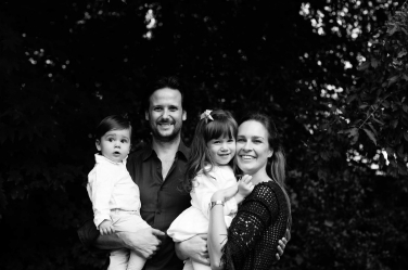 A black and white family portrait of a couple, their daughter and son.