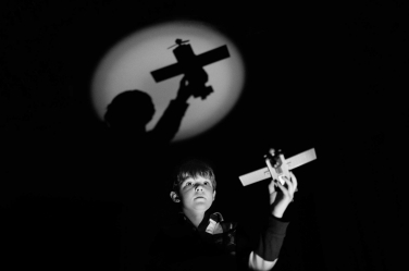 A boy flies a plane in the dark and his imagination, in this dramatic child's portrait from London photographer Helen Bartlett.