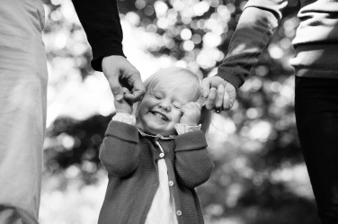 A little girl screws up her face with glee as she gets to hold the hands of both her parents during a family portrait shoot.