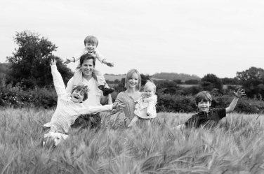A family of four hides in the grass during their portrait shoot in black and white.