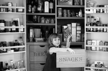 A shopkeeper in the making: this girl works her way through the family larder.