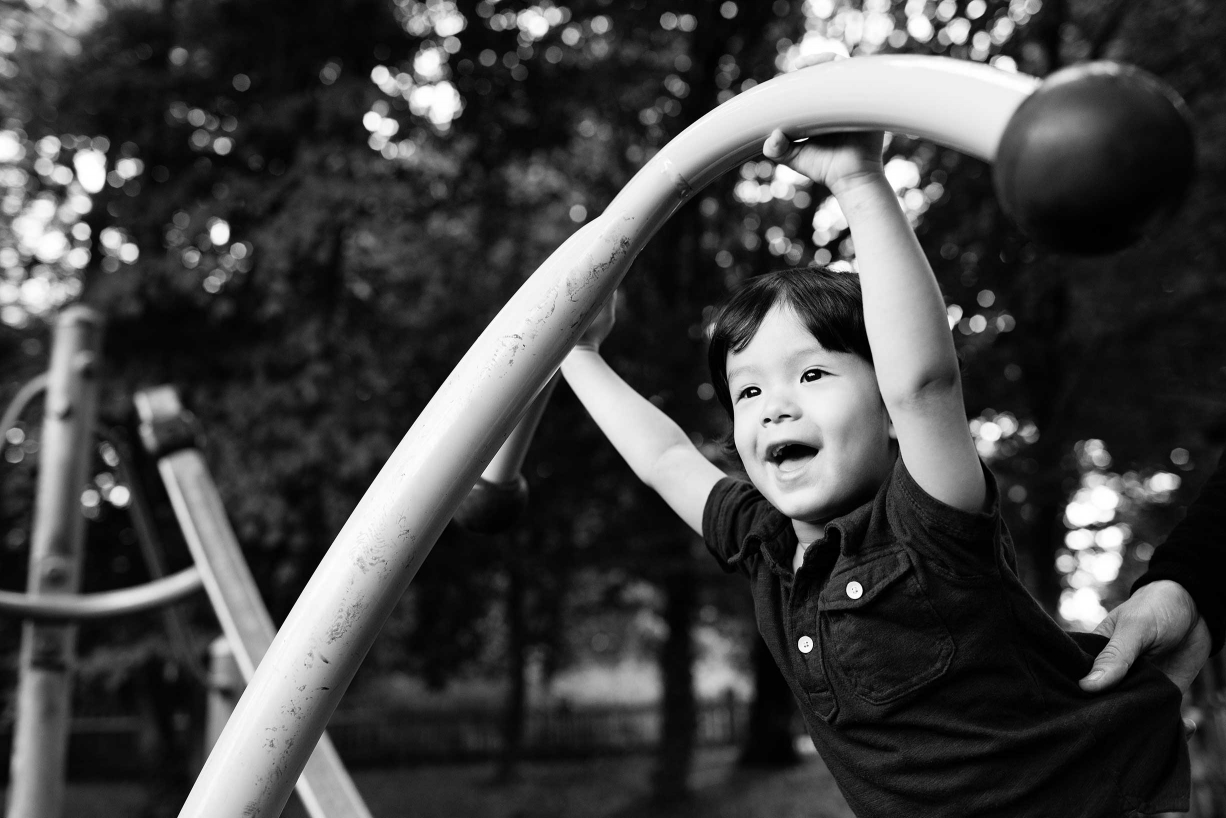 The dramatic shape of playground equipment gives this child's portrait a strong leading line that adds drama and life to this black and white portrait.