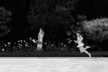 A spring portrait with a small girl leaping into a pool.