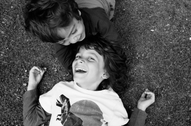 Two brothers lie on the ground during their family photos, giving an opportunity for a downward portrait view.