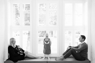 A family of four portrait taken inside a shuttered window.