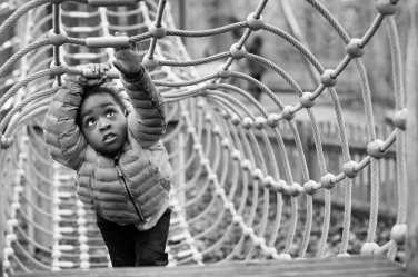 This child concentrates fully on getting across the playground nets.