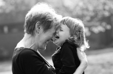Grandma and her granddaughter giggle together during their family portraits. Multiple generations are often included in lifestyle portraits by London photographer Helen Bartlett.