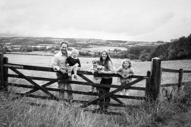A family portrait using a farm gate as a gathering point for the family.