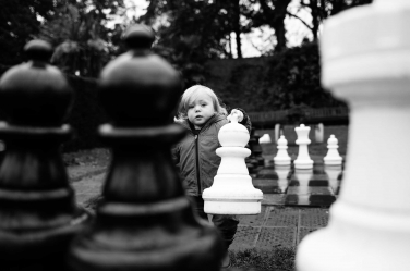 Your move! A little girl grabs an oversized chess piece during a London lifestyle portrait shoot.