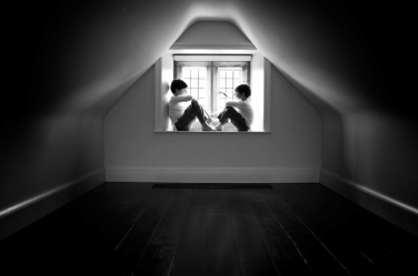 Two brothers hide out in their attic in this lifestyle portrait in black and white.