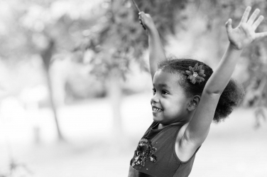 Yippee! This girl cheers for joy in a family lifestyle photo taken by professional photographer Helen Bartlett.