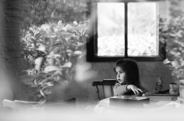 Shot from outside: London photographer Helen Bartlett captures this moment of quiet contemplation from a little girl at her family table.