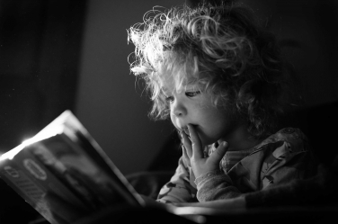 A cute little girl is enthralled by her story book.