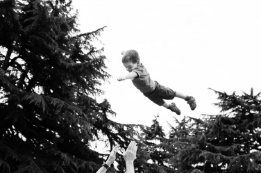 A small boy flies through the air in this casual park portrait session.