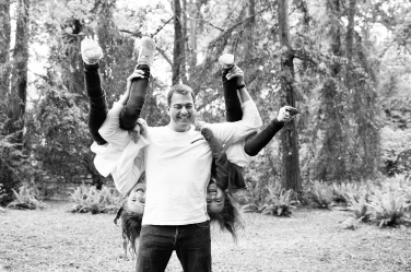 Being a dad can be a juggling act: this one holds two of his daughters upside down.