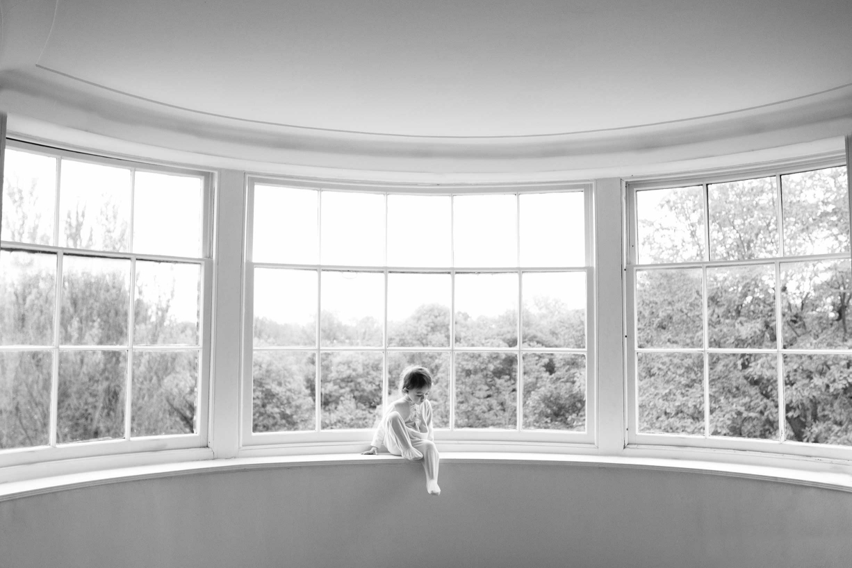 A tiny child sits in a window for this timeless portrait in black and white