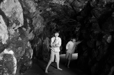 Two brothers explore sea caves in this black and white photo of family adventures.