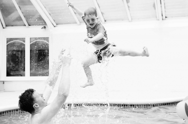 A small boy is flung in the air by his father in this lifestyle family portrait