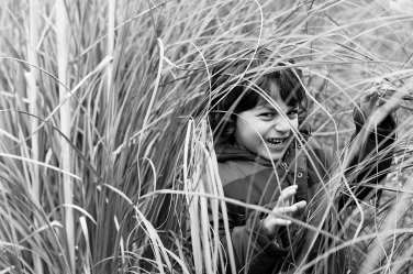 A tiny tiger of a girl growls through the long grass in this black and white family portrait.