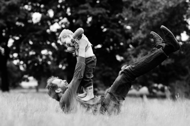 A toddler dances on his father's tummy in the long grass of a London park.