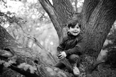 A boy does his best squirrel impression for this tree portrait in black and white.