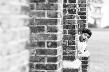 An expression can make a portrait, as it does in this one of a boy looking around a brick wall.