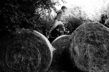 London photographer Helen Bartlett captures this small boy mid-air, leaping from one hay bale to another.