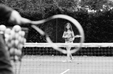 A tennis racquet frames a girl concentrating on her match.
