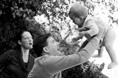Mother and father swing their baby around with joy.