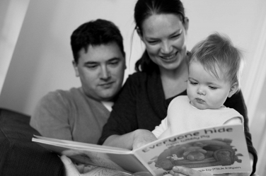 Parents read their toddler daughter a story together.