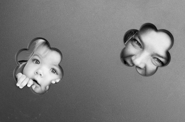 Mother and daughter peer through cut-outs in a family photo shoot.