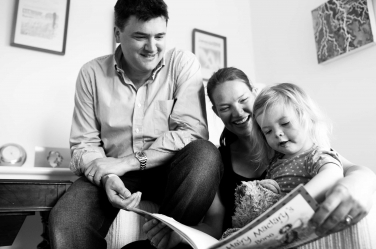 A black and white photo of a family reading a story together.