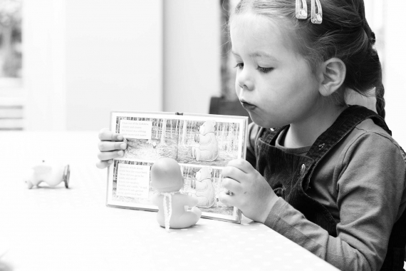 A little girl reads a book to her baby doll in this black and white photo.