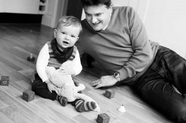 Toddler boy and his father with a teddy bear on the floor for a family photo.