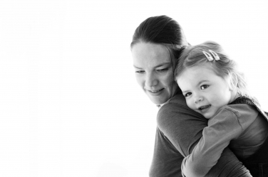 A little girl hugs her mother. The portrait is back-lit.