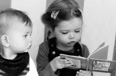 A little girl reads a book to her toddler brother.
