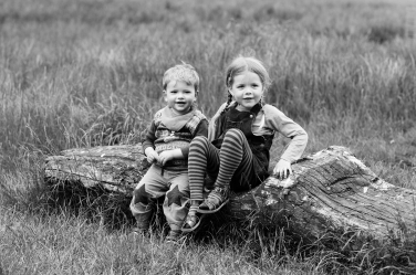 A brother and sister sit on a log in a field for their family portraits.