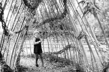 A girl runs through a wooden arbour during a family photo.